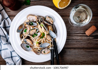 Traditional italian seafood pasta with clams Spaghetti alle Vongole on wooden background. Top view