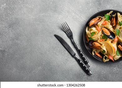 Traditional italian seafood pasta with clams Spaghetti alle Vongole on stone background. Top view