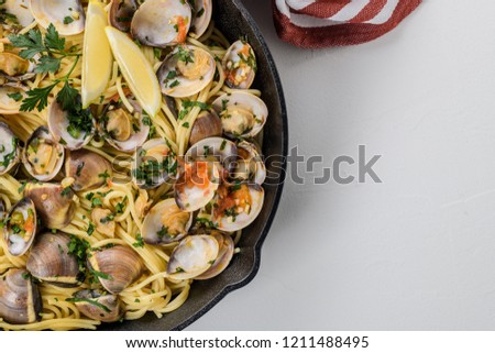 Traditional italian seafood pasta with clams Spaghetti alle Vongole. Flat lay top-down composition.