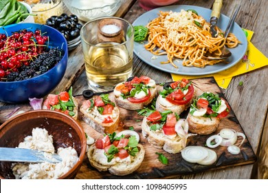 Traditional Italian snacks at dinner table, classic pasta with tomato sauce, olives bruschetta, cherry tomatoes, mozzarella close up. The concept: the abundance of products.
