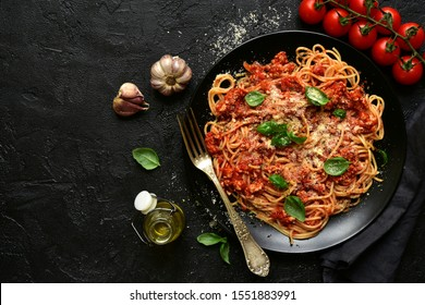 Traditional italian spaghetti bolognese on a black plate on a dark slate, stone or concrete background. Top view with copy space.