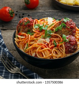 Traditional Italian spaghetti with meatballs and parmesan in tomato sauce in a black bowl. American family meal on a table.