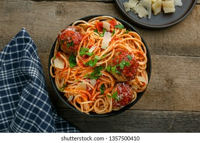 Traditional Italian spaghetti with meatballs and parmesan in tomato sauce in a black bowl. American family meal on a table. Top view shot.