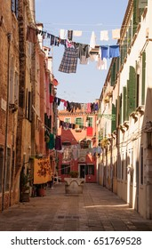 Traditional Italian street with clothes hanging out to dry between old houses