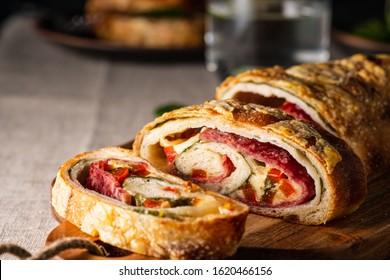 Stromboli italien traditionnel farci de fromage, salami, poivre rouge et épinards. Photo dans un style sombre.