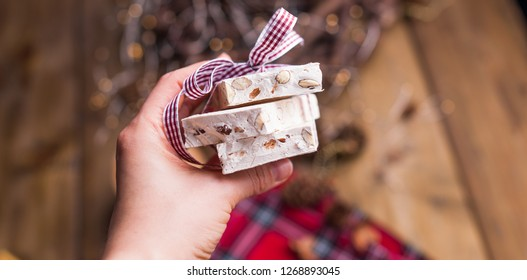 Traditional Italian sweet from nougat and almond for Christmas. Candy in a female hand. Free space for text