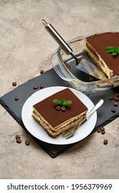 Traditioneller italienischer Tiramisu-Dessert auf grauem Betonhintergrund