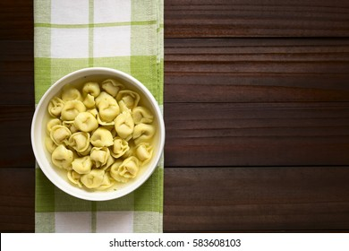 Traditional Italian Tortellini in Brodo (broth) soup, photographed overhead on dark wood with natural light