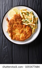 Traditional Italian veal Milanese with lemon and French fries close-up on a plate. Vertical top view from above