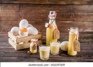 Traditional Italian Vov eggs liquor. German Egg Liqueur Eierlikor. In different bottle and shot glasses, Wooden background copy space