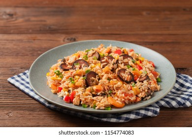 Traditional jambalaya perepared in wok, serwed on plate. Front view.