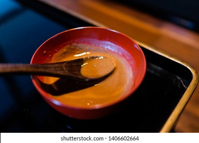Traditional japanese bowl in restaurant with black lacquered wood table background and miso sauce and spoon