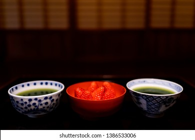 Traditional japanese bowls cups with matcha green tea and strawberries in machiya house with black lacquered wood table and dessert dish