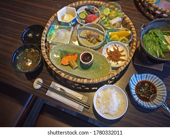 Traditional Japanese breakfast ryokan meals set served in round tray on the table, appetizers, tofu soup on fire, fried fish and rice bowl
