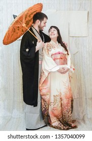 Traditional Japanese ceremony wedding lovely day,  married couple holding orange paper umbrella in hands, isolated on kimono material background.