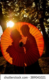 Traditional Japanese ceremony wedding lovely day, silhouettes of married couple holding red paper umbrella in hands, kissing under golden sunset in shrine temple garden, colorful maple ginkgo leaves