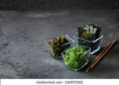 Traditional Japanese Chuka Wakame seaweed salad and crispy roasted nori sheets in glass bowl on dark background top view with copy space.Asian japanese chuka.Organic natural product.Raw vegan food