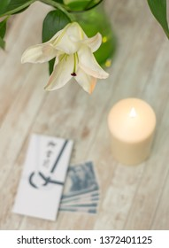 Traditional Japanese condolence funeral envelope with Yen currency, with candle and lily