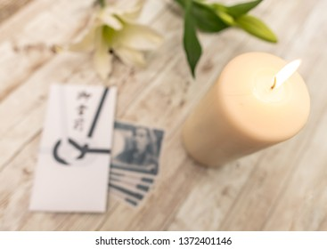 Traditional Japanese condolence funeral envelope with Yen currency, with candle