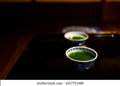 Traditional japanese cups with matcha or mulberry green tea in ryokan with black lacquered wood table