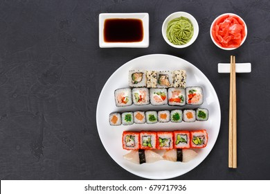 Traditional japanese food restaurant. Colorful sushi set served on white platter with chopsticks, soy sauce, ginger and wasabi. Top view on gray background with copy space
