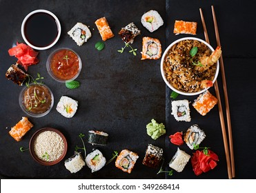 Traditional Japanese food - sushi, rolls, rice with shrimp and sauce on a dark background. Top view