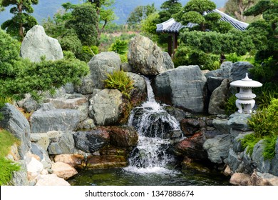 Traditional Japanese garden. Decorative waterfall, a stream among the stones on the background of exotic well-groomed trees and flowering shrubs.