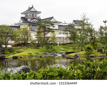 Traditional Japanese garden with pond and white castle in Toyama, Japan
