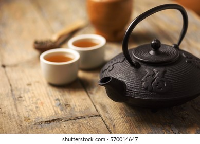 Traditional japanese herbal tea recipe prepared in cast iron teapot with organic dry herbs. Alternative medicine. Healthy asian green tea in tea pot on vintage wooden table background.