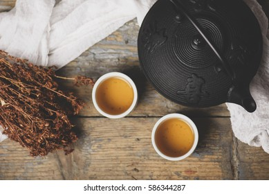 Traditional japanese herbal tea recipe prepared in cast iron teapot with organic dry herbs. Top view of asian traditional hot beverage on wooden table.