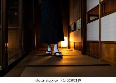 Traditional japanese house or ryokan with man in kimono walking closeup of legs with geta tabi shoes and socks by shoji sliding paper doors and tatami mat floor