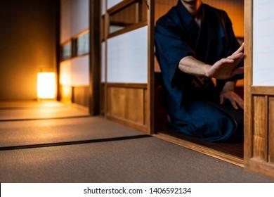 Traditional japanese house or ryokan with man in kimono opening shoji sliding paper doors sitting on tatami mat floor