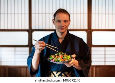 Traditional japanese house or ryokan restaurant with salad plate and man in kimono or yukata background of shoji doors