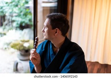 Traditional japanese house or ryokan restaurant with man in kimono or yukata looking at garden eating anko dango
