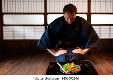Traditional japanese house or ryokan restaurant with black lacquered table and salad dish with man in kimono or yukata background of shoji doors