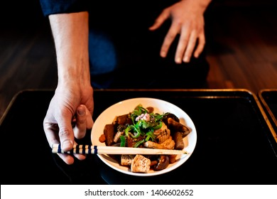 Traditional japanese house or ryokan restaurant with black lacquered wood table and dish closeup with man in kimono or yukata picking up chopsticks