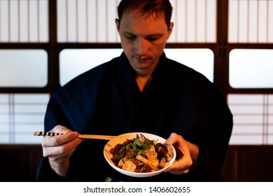 Traditional japanese house or ryokan restaurant with closeup of man in kimono or yukata eating konnyaku dish with shoji sliding paper door
