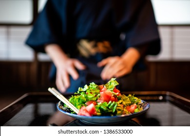Traditional japanese machiya house or ryokan restaurant with black lacquered wood table and salad dish closeup with man in kimono or yukata background