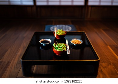 Traditional japanese machiya house or ryokan restaurant with black lacquered wood table and edamame food with natto and soy sauce