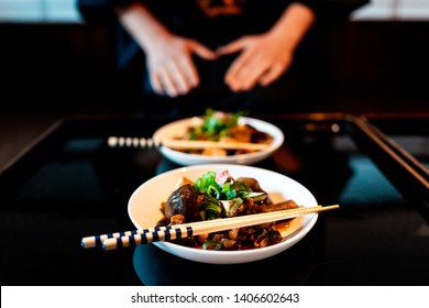 Traditional japanese machiya house or ryokan restaurant with black lacquered wood table and dish closeup with man in kimono or yukata background