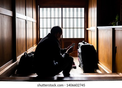 Traditional japanese machiya house or ryokan with sliding paper door entrance and light with man sitting holding phone architecture