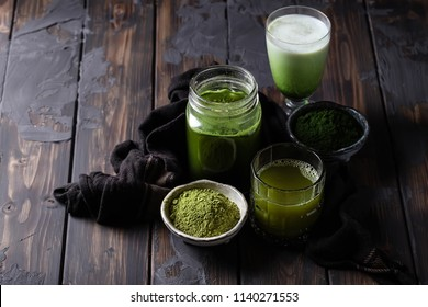 Traditional Japanese Matcha tea together with Iced Matcha Latte drink decorated with matcha powder and napkin over rustic wooden background