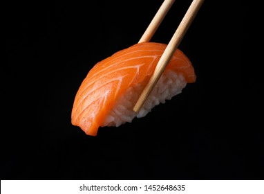 Traditional japanese nigiri sushi with salmon placed between chopsticks, separated on black background side view