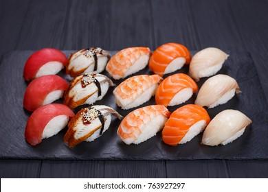 Traditional Japanese nigiri sushi set on black stone slate. Delicious seafood, sushi restaurant concept