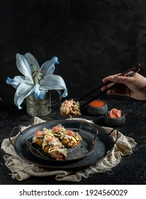 traditional Japanese octopus takoyaki presented on a rustic metal tray with pickled ginger and spicy sauce. in a dark background. feminine hand picking one takoyaki with jock sticks.