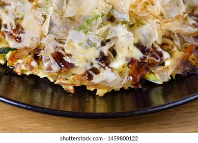 traditional Japanese omelette Okonomiyaki, with eggs, Savoy cabbage, mayonnaise, carrot, zucchini, ginger, dried seaweed and Katsuobushi, okaka, flakes of dried meat from skipjack tuna