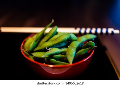 Traditional japanese plate bowl in restaurant or ryokan kaiseki with vegetable dish snack of boiled edamame with salt and green color closeup chopsticks