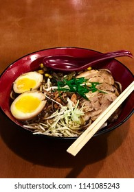 Traditional japanese pork lamen on the red bowl on wood backgrou