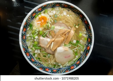 Traditional Japanese ramen with salt based soup, sliced pork, sliced egg, bamboo shoot and green onion. On Table. Asian style food. Top view.