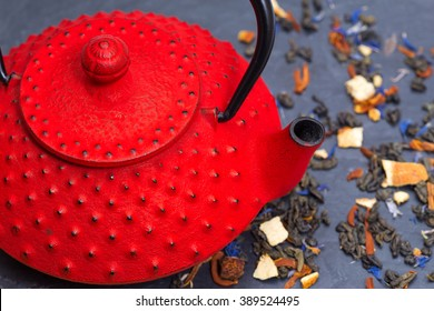 Traditional Japanese red teapot and tea leaves on black slate
